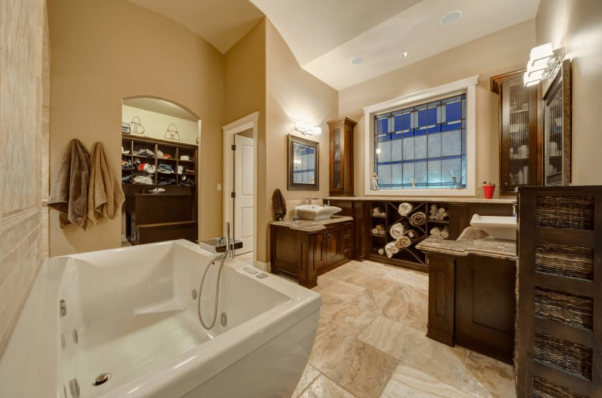 Beige bathroom with a deep soaking tub and facing sink vanities across the storage cabinet accented by a stained glass window.