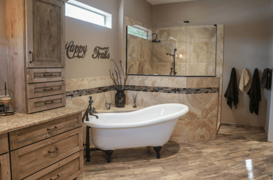 Cozy bathroom showcases rustic cabinetry blending in with the beige flooring and walls accented by stunning mosaic tiles. It includes a clawfoot tub and walk-in shower with antique bronze fixtures.