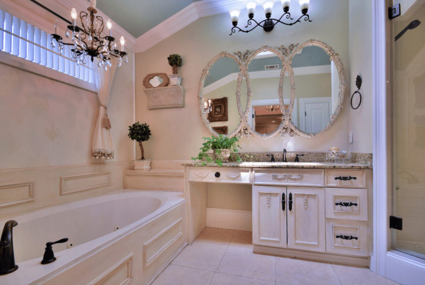 Fabulous bathroom with a French country style featuring clustered mirrors and deep soaking tub lighted by wrought iron chandelier and ornate wall sconce.