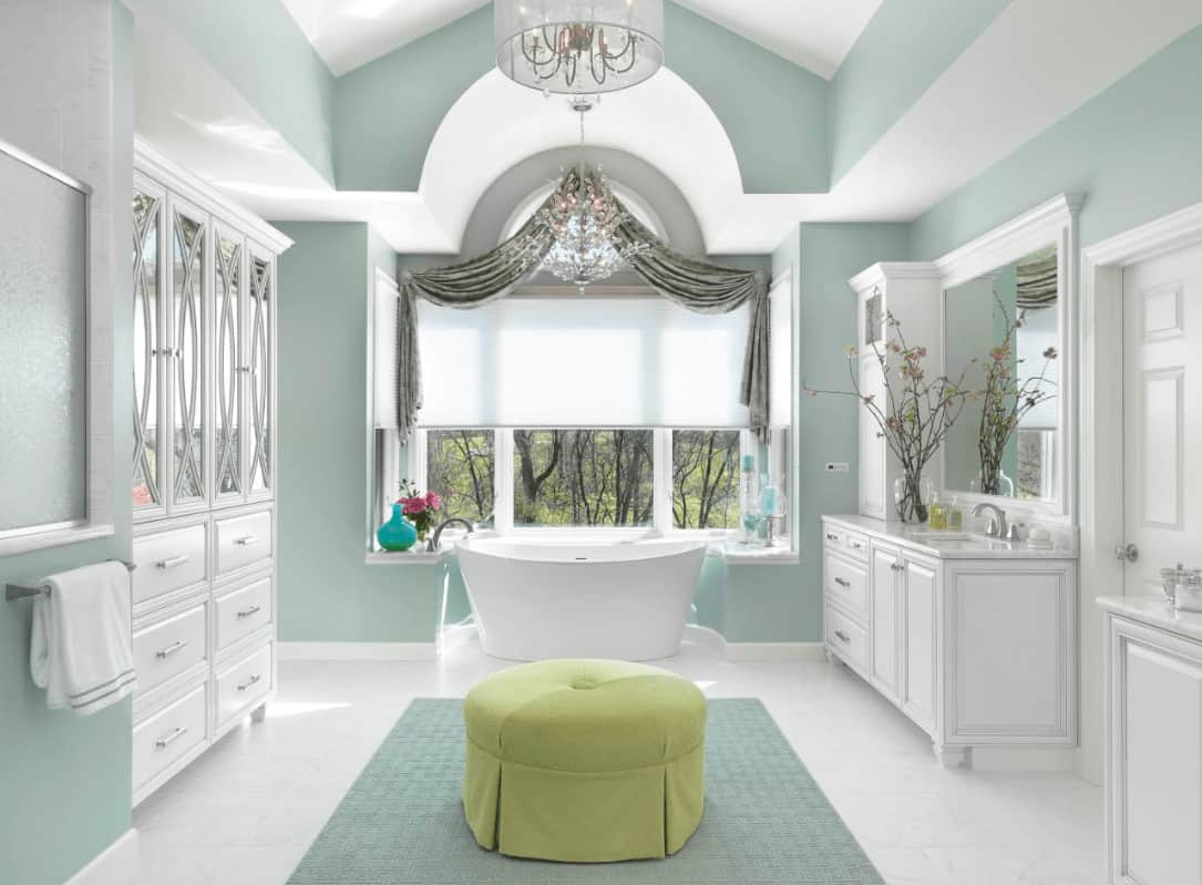 Luxury bathroom illuminated by fancy chandeliers that hung over the freestanding tub and green skirted ottoman. It has muted blue walls and glass paneled windows overlooking the enchanting forest.