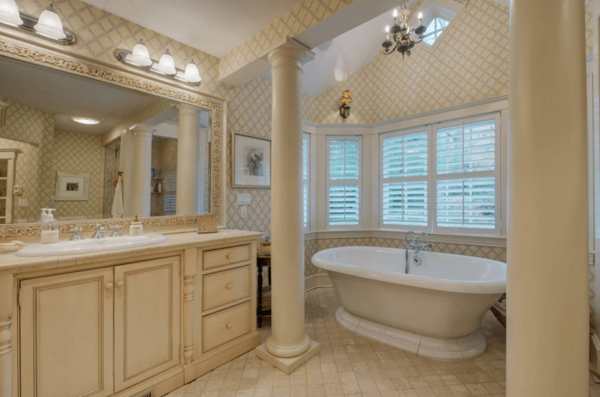 Country style bathroom offers a single sink vanity with charming carved wood mirror and a pedestal bathtub lined with large columns.