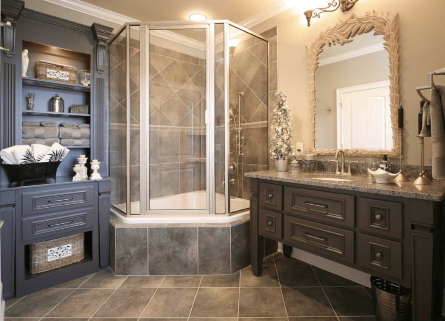This bathroom is filled with dark wood vanity paired with a stylish mirror and a blue storage cabinet that sits next to the walk-in shower enclosed in glass.