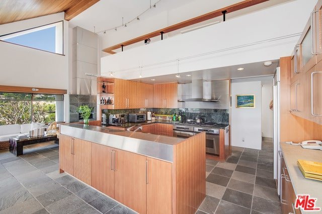An open kitchen with wooden cabinetry and a center island topped with a stainless steel countertop that matches the appliances. It has concrete tiled flooring and glazed windows bringing an abundance of natural light in.