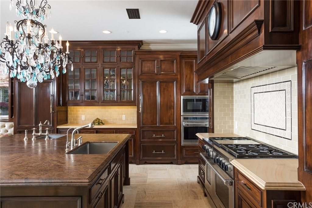 A fabulous crystal chandelier illuminates the granite top island that's fitted with undermount sinks and chrome fixtures. It is surrounded by inset appliances and wooden cabinetry along with a cooking alcove that's accented with a white subway tile backsplash.
