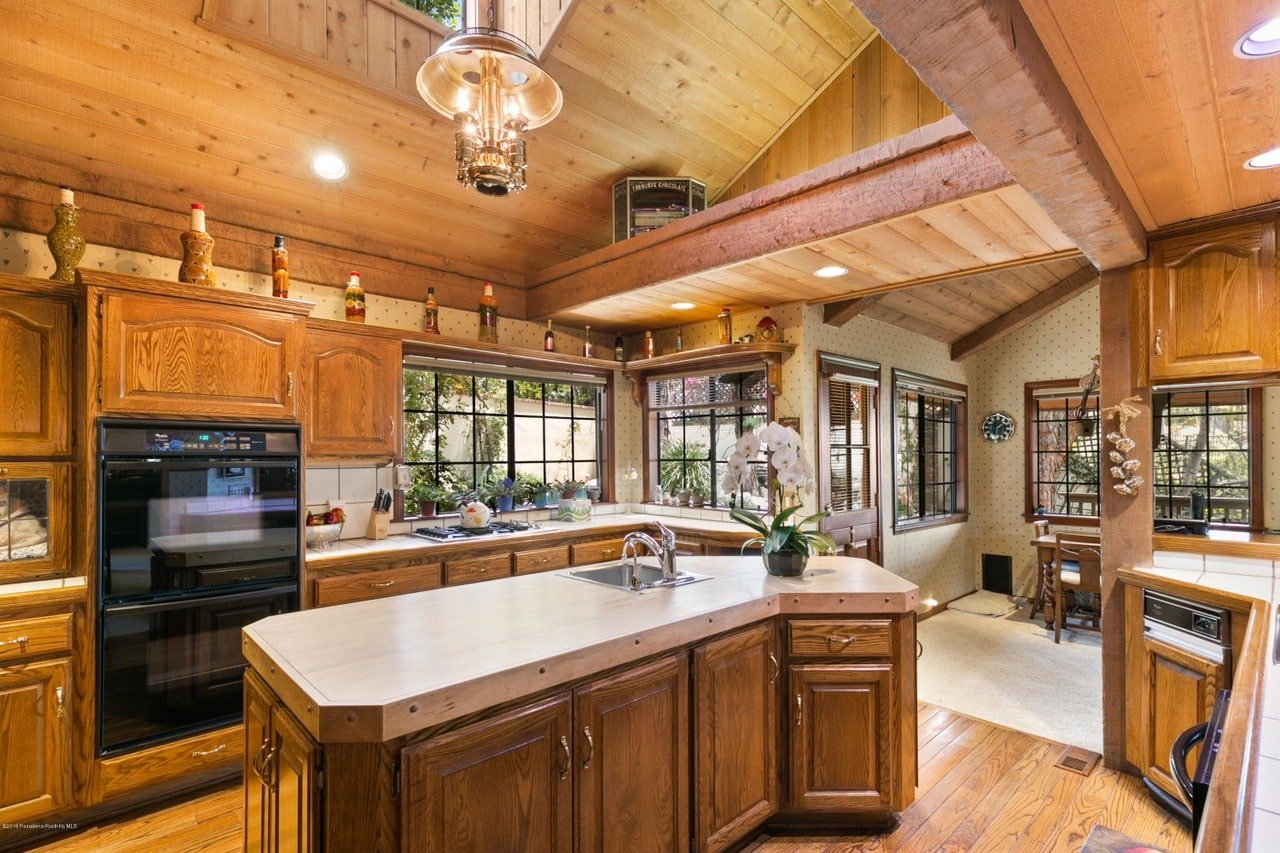 Cozy kitchen boasts black appliances and wooden cabinetry matching with the island bar that's fitted with an undermount sink and chrome fixtures. It blends in with the wood plank ceiling and hardwood flooring maintaining a cohesive look.