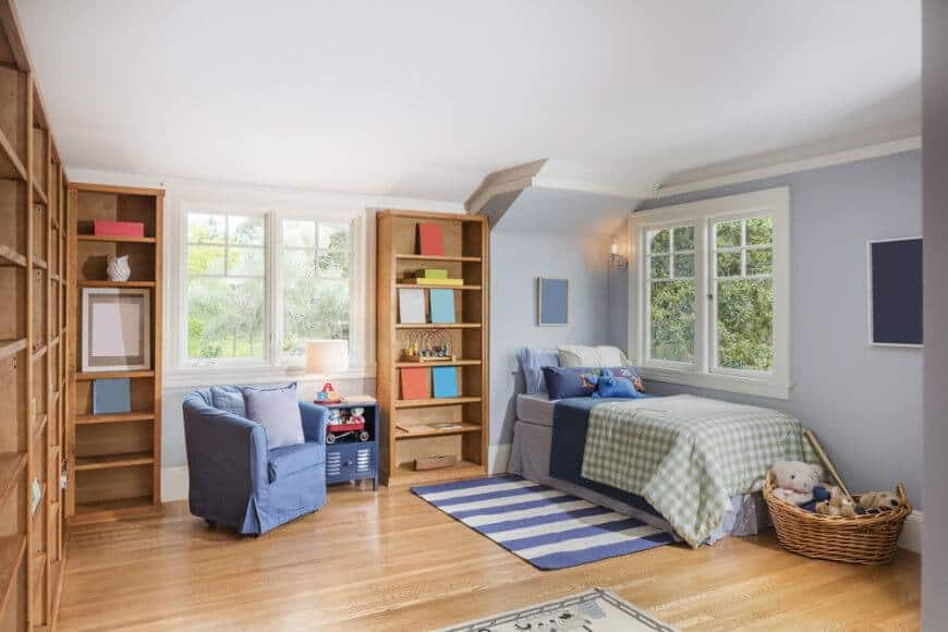 This boy's bedroom features a walnut finished shelving and hardwood flooring paired with the light gray walls. The bed is placed near the window.