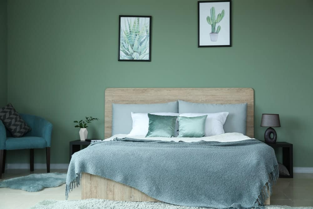 The bare wooden headboard of the traditional bed is a nice complement for the light green hue of the wall that is adorned with a couple of framed artworks of plants.