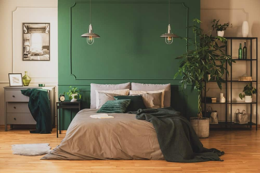 The dark green matte wall at the head of the bed is a nice background for a couple of industrial pendant lights hanging over the side of the bed that has gray sheets complementing the hardwood flooring.