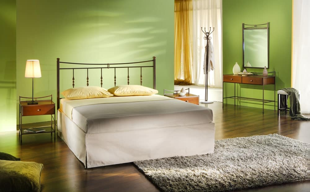 This is a simple bedroom with a simple white bed that has a thin iron railing headboard that stands out against the green walls. The hardwood flooring is topped with a furry gray area rug.
