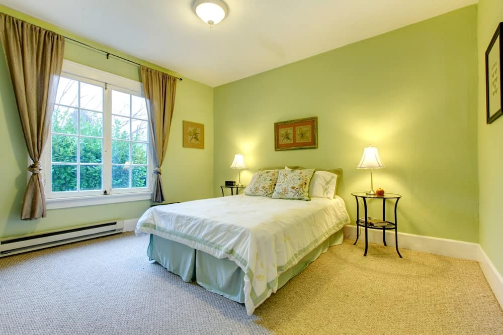 The light green walls are paired with the light green sheets of the cottage bed that is flanked two circular bedside tables bearing table lamps.