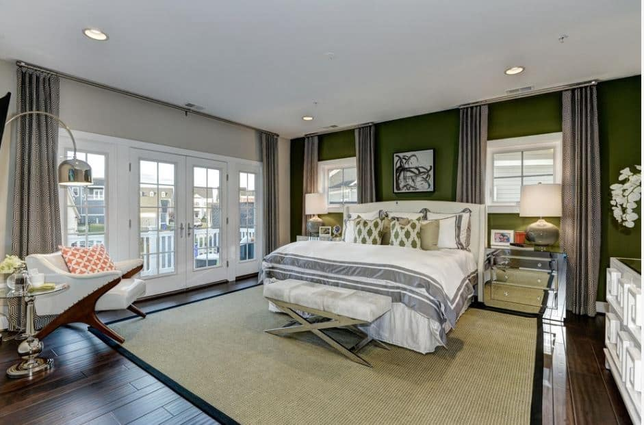 The traditional bed with a white cushioned headboard is wonderfully contrasted by the dark green wall adorned with a black and white artwork flanked by two square French windows.