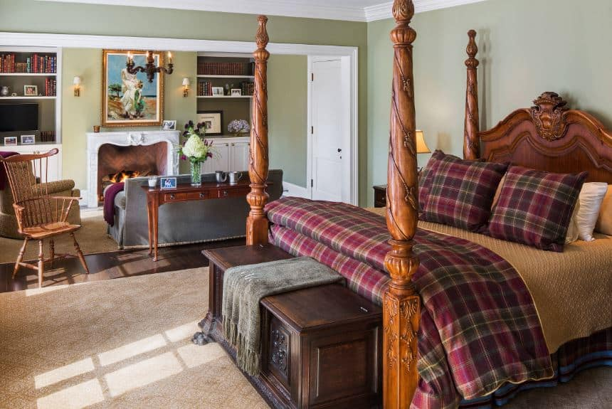 The wooden four-poster bed has intricate carvings that match the wooden footlocker that contrasts the beige area rug and green walls paired with a white ceiling.