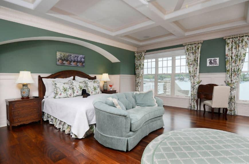 The white coffered ceiling is a nice match for the arched alcove of the green wall by the wooden headboard of the traditional bed that stands out against the white wainscoting as well as the wooden bedside drawers.