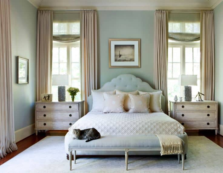 This is a simple and chic primary bedroom that has a pair of distressed bedside drawers flanking the light green headboard of the traditional bed that has a low cushioned bench at the foot of the bed matching the green walls.