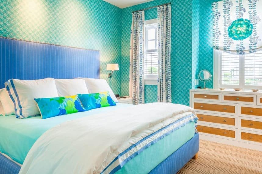The walls are dominated by bright green wallpaper that has intricate designs contrasted by the simple white ceiling and the striped green cushioned headboard of the traditional bed.