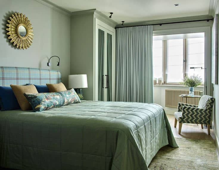 The brilliant windows are paired with light green curtains that blend with the green walls that have a golden wall-mounted sun-like artwork above the cushioned headboard.