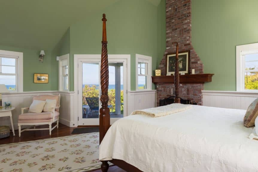 The wooden pencil posters of this bed have elegant intricate carvings that provide a nice contradiction to the smooth green walls that are adorned with a fireplace inlaid with brick that goes up the wall to the arched green ceiling.