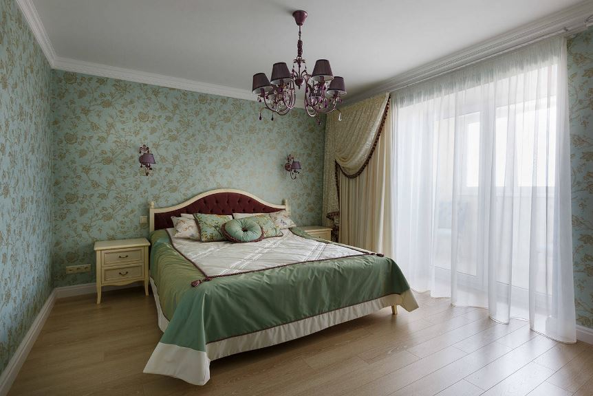 The chic grape-colored chandelier is perfectly matched with the pair of wall-mounted lamps above the maroon cushioned headboard that stands out against the floral green wallpaper of the walls.