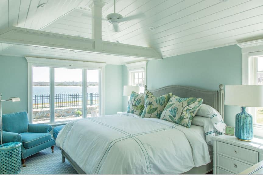 The bright and cheerful pastel green hue of the walls is further brightened by the white cove ceiling and the natural light coming in from the tall windows framed with white molding that contrast the gray bed.