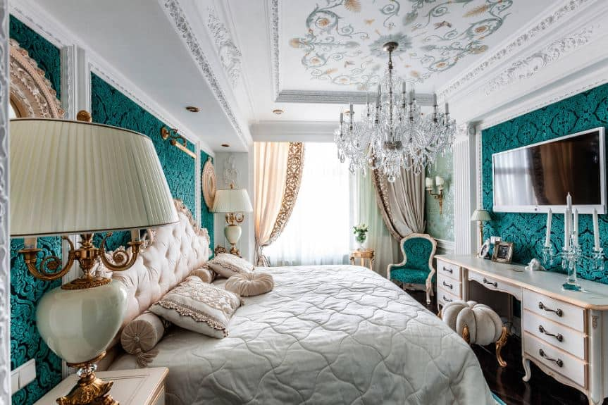 This bright bedroom has elegant intricate designs on its green walls and white tray ceiling that hangs a brilliant crystal chandelier over the traditional bed with a pink cushioned headboard.