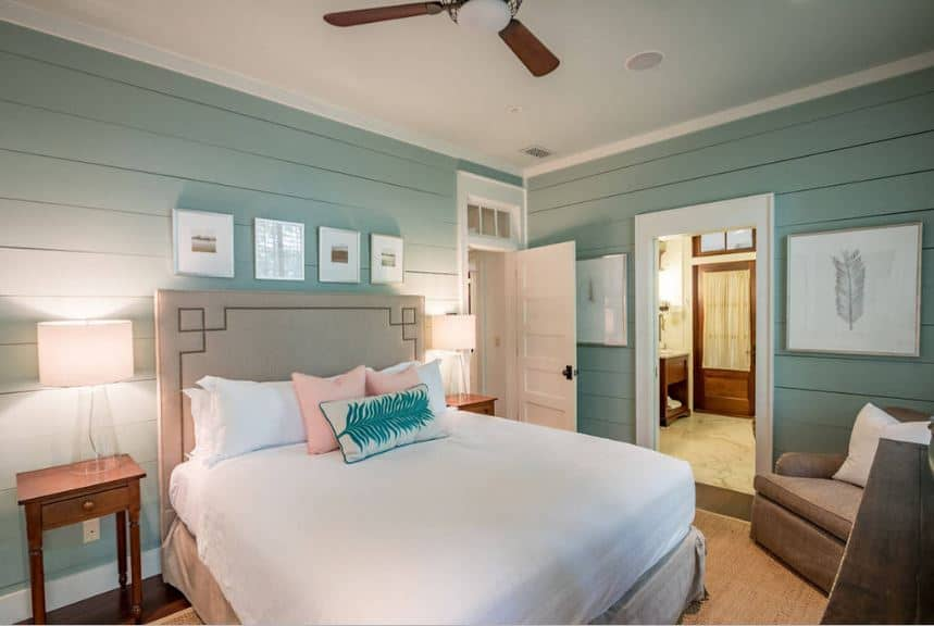 This bedroom has pastel green shiplap walls complemented by simple wall-mounted artwork over the beige headboard flanked by wooden bedside tables.