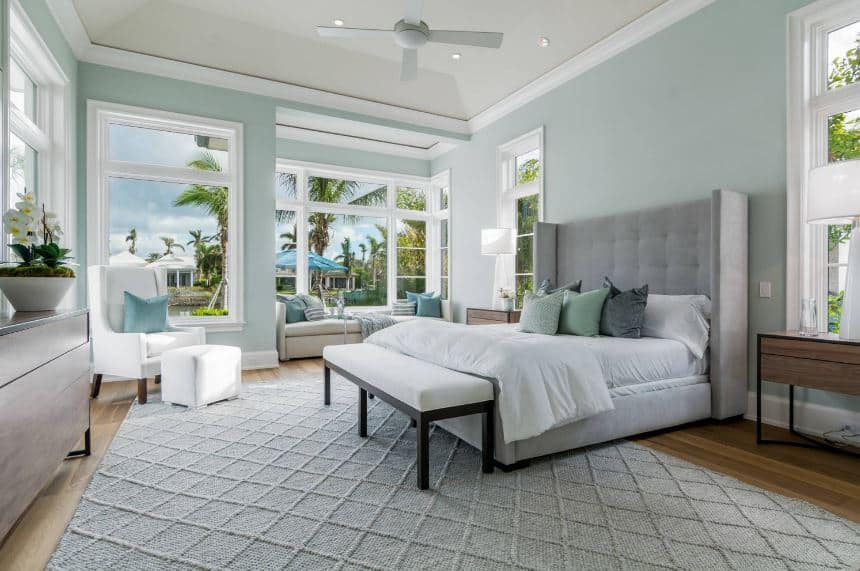 This is an airy and spacious master bedroom with a high white cove ceiling complemented by pastel green walls filled with massive glass windows that illuminate the gray bed and area rug.