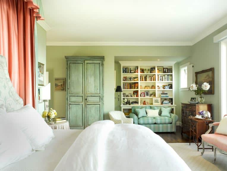 The green distressed cabinet and striped sofa match the green walls of this master bedroom with a charming reading area in a corner that has a bookshelf.
