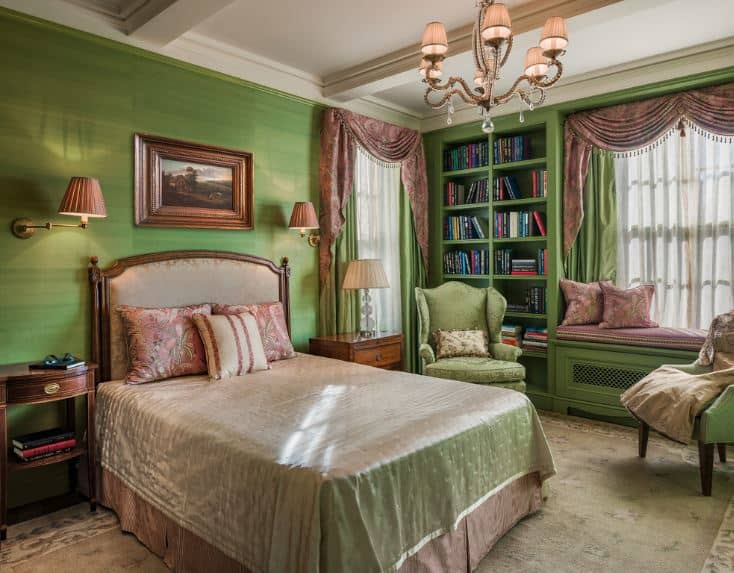 The avocado green walls are a perfect match for the white coffered ceiling and beige area rug underneath the traditional bed with beige sheets and headboard.