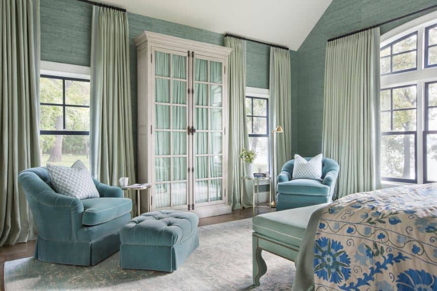 The high white arched ceiling contrasts the walls that have a green wallpaper covering it. This is paired with white tall windows and a pair of velvet cushioned armchairs with a similar green hue.