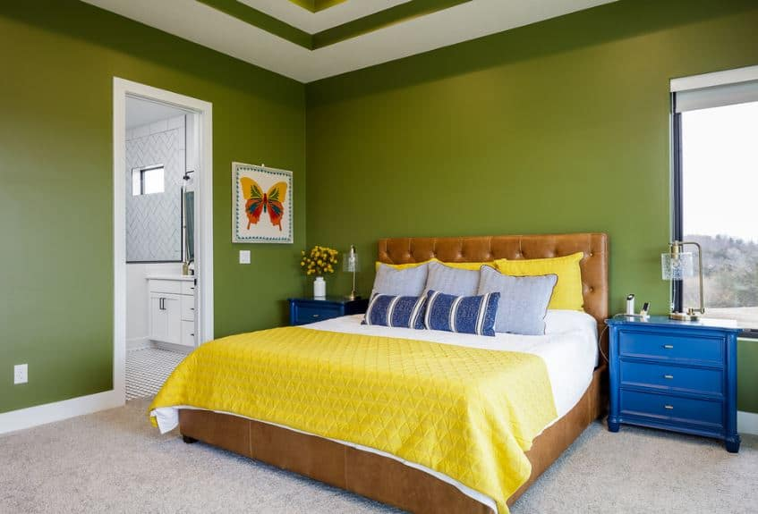 This is a master bedroom dominated by the primary colors of green walls and ceiling, blue bedside drawers and yellow bedsheets of the bed that has a brown leather cushioned headboard.