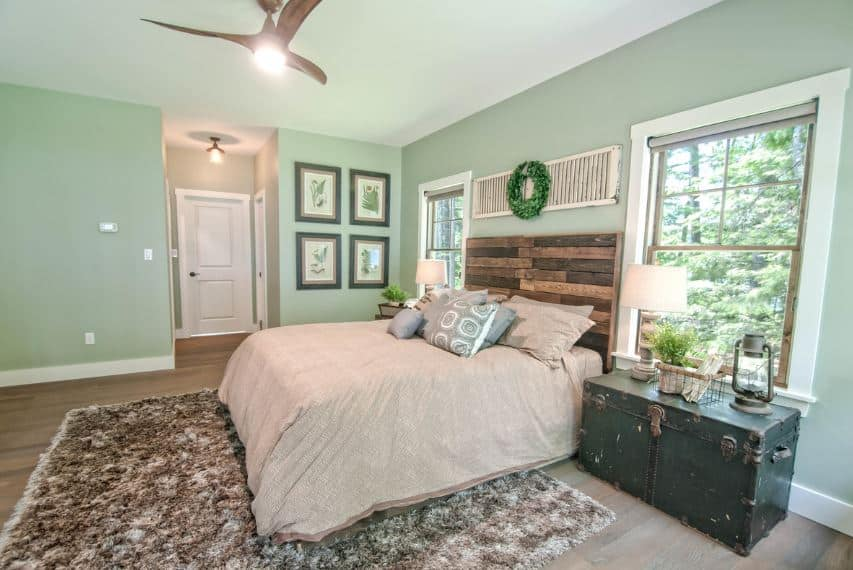 The cheerful light green shade of the walls is paired rustic elements from the green footlocker and the plank wood headboard of the traditional bed.