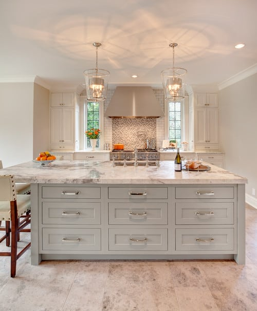 Large Mediterranean kitchen with tiles flooring and white walls. The center island featuring a marble countertop offers space for a breakfast bar lighted by elegant pendant lights.