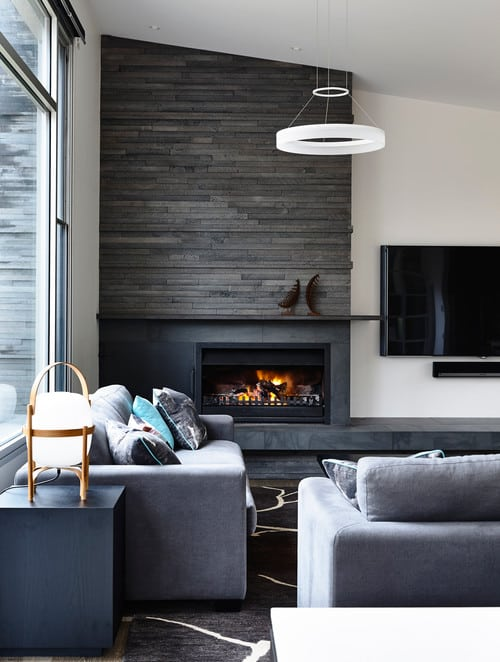 A living room space with a fireplace covered with brick accent