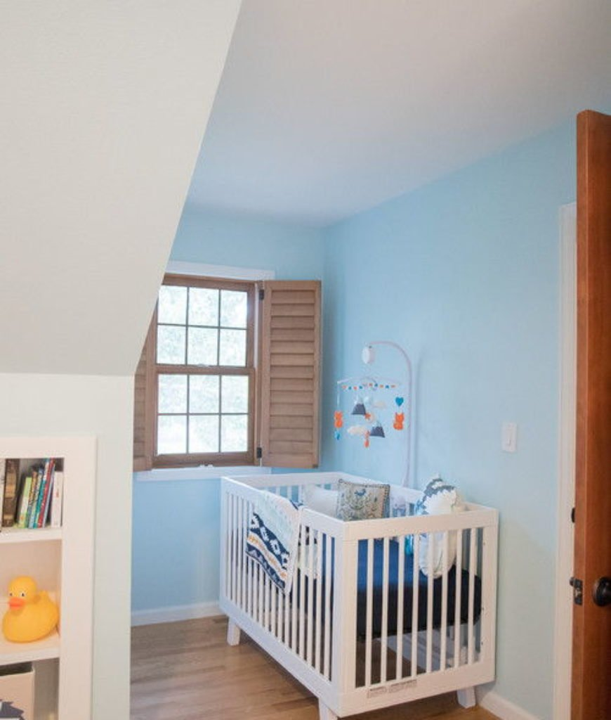Contemporary modern interior remodel nursery bedroom with laminated flooring and small window.