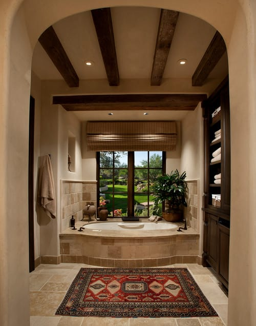 Here's a Mediterranean style primary bathroom with a large separate bathtub alcove area with built-in shelving next to on one side and a large window looking out onto manicured lawns on the other side.