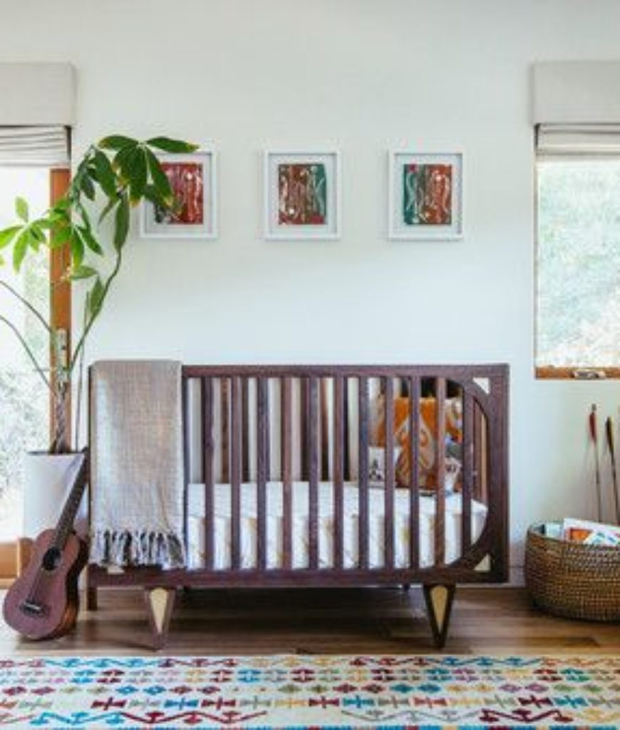 Midcentury white nursery bedroom with hardwood flooring and indoor container plant.