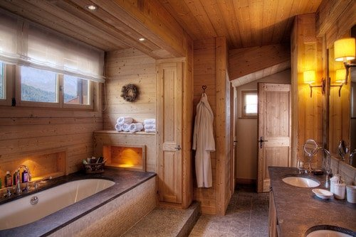 Here's a sauna-like primary bathroom with wood walls and ceiling. The alcove tub is surrounded with wood and mood lighting.
