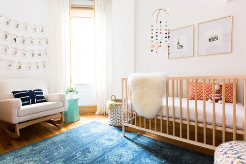 Scandinavian bright pink nursery bedroom with blue rug and white rocking chair.