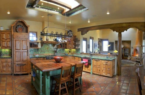 Large open-concept kitchen with wood cabinetry, green tile backsplash, and a hanging potrack above the green kitchen island with wood surface.