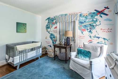 Transitional nursery bedroom with world map wall design and blue rug.