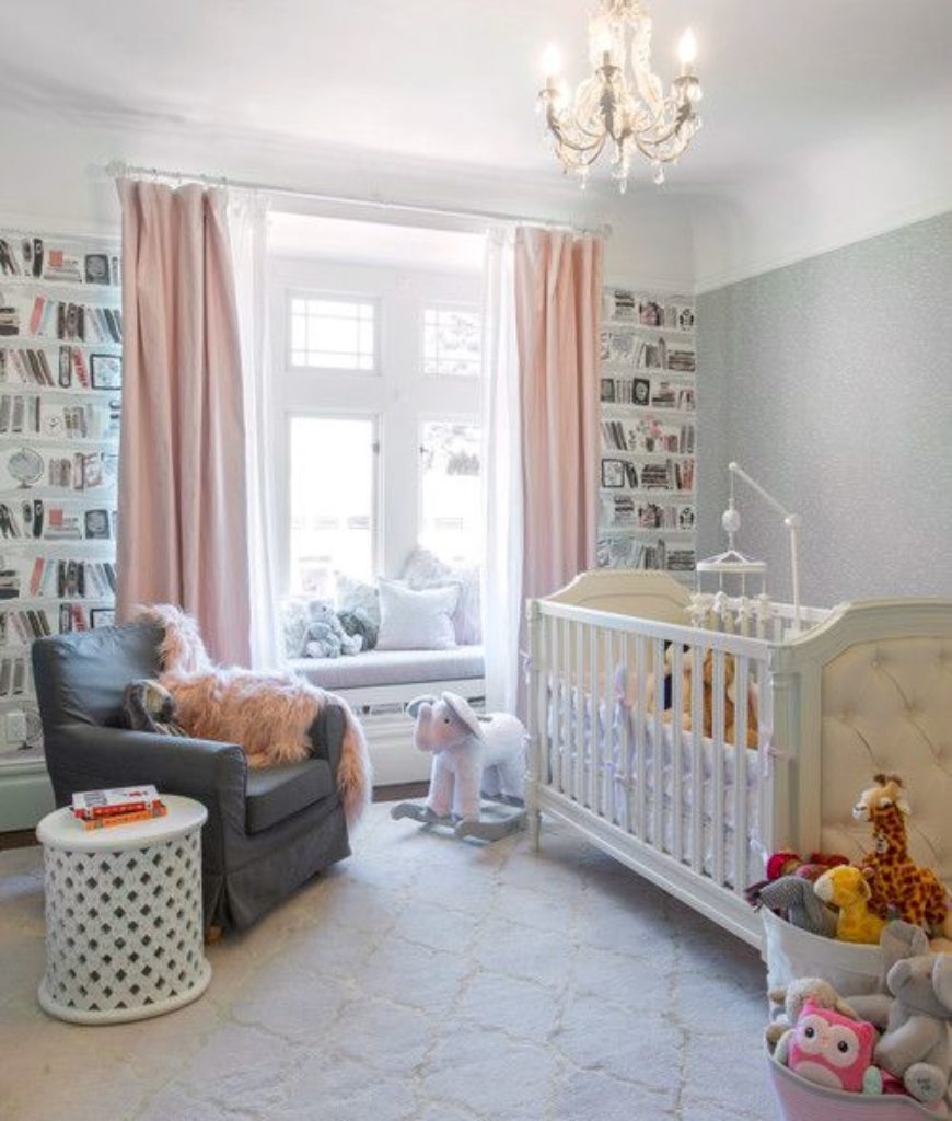 Transitional nursery bedroom with elegant-looking chandelier and carpet flooring.