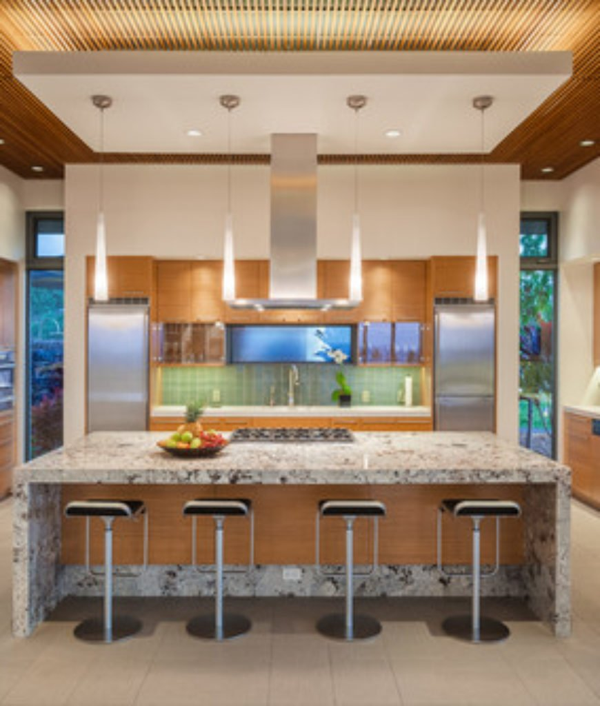 A large tropical kitchen with an island with stone countertop