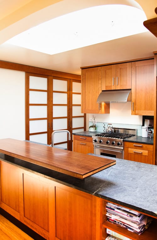 Asian kitchen with all around woodwork from the wood-framed sliding doors to the cabinetry and from the peninsula island with wood surface to wood flooring.
