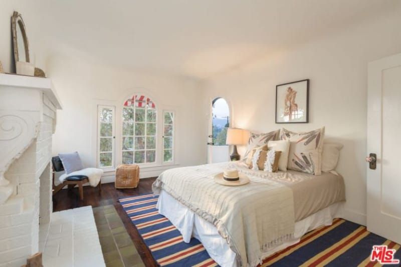 Master bedroom featuring white walls and ceiling. The room also offers a comfy bed and a fireplace.
