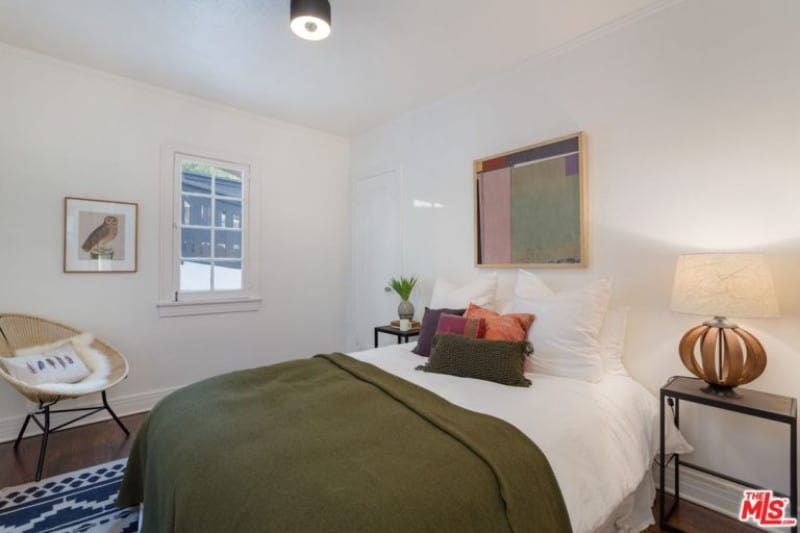 This small minimalist guest room painted in white features simple design with a side lamp, framed artworks and a small casement window.
