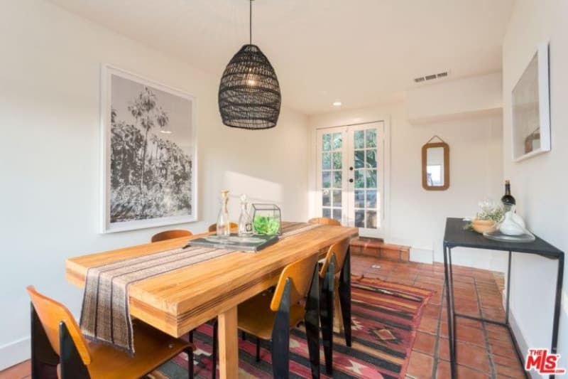 White dining room with a french door and terracotta flooring topped with a red patterned rug. It has a wooden dining set illuminated by a black rattan pendant light.
