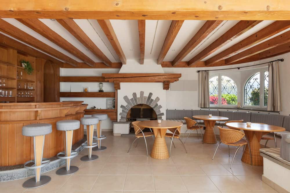This man cave features a wooden bar matching the dining nook sets and the beams on the ceiling.