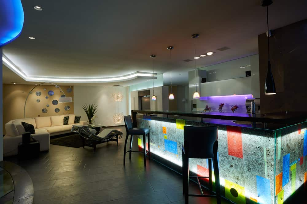 Large modern man cave where the neon base lit bar is the highlight. The long black-top neon base lit bar faces toward a curved beige sectional sofa and comfortable chaise lounge in the lounge ear.