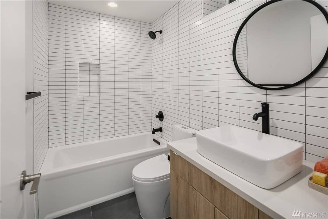 This Scandinavian-Style bathroom has white-tiled walls fitted with black grout to emphasize the straight lines of the tiles. This theme is complemented by the black fixtures of the room and the frame of the circular wall-mounted vanity mirror.