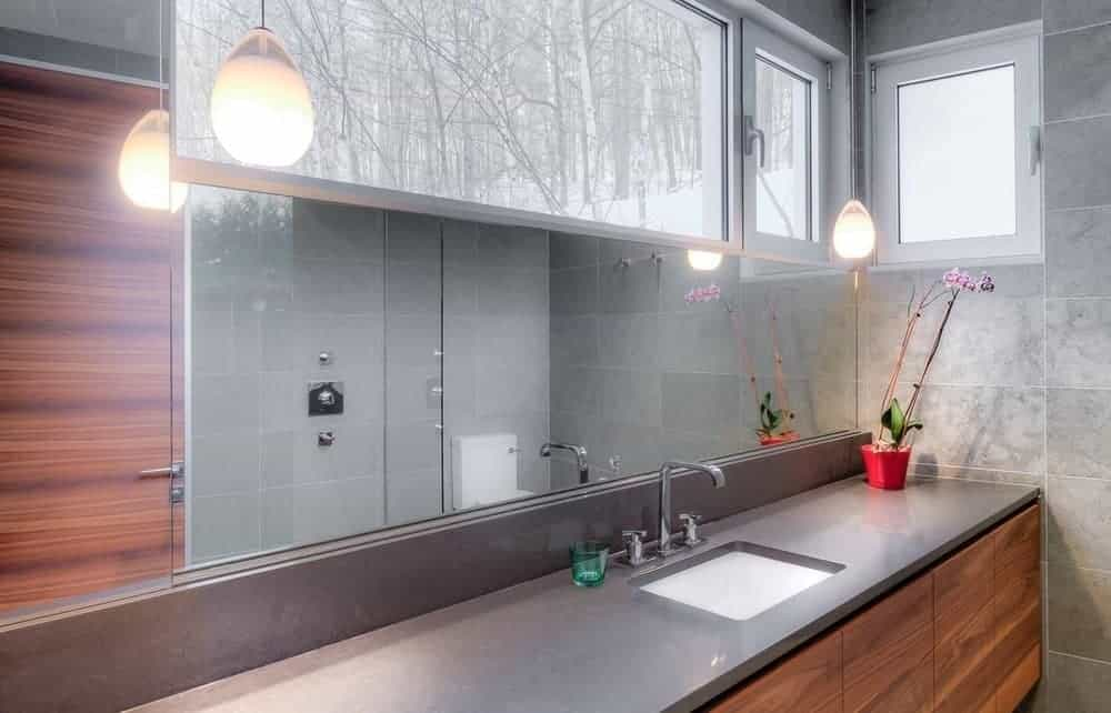 This is an elegant and bright bathroom with a gray countertop and backsplash for the vanity area that has white sink paired with a modern dual-knob faucet and a wide mirror. This mirror is built into the wall and seamlessly connects with the narrow window above it.